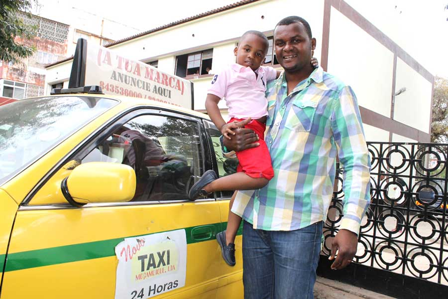 Mozambican taxi driver holding his son