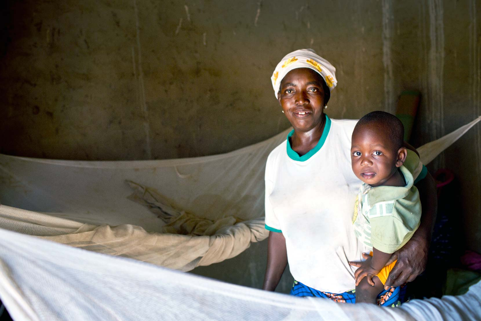 Mother and baby setting up bed nets