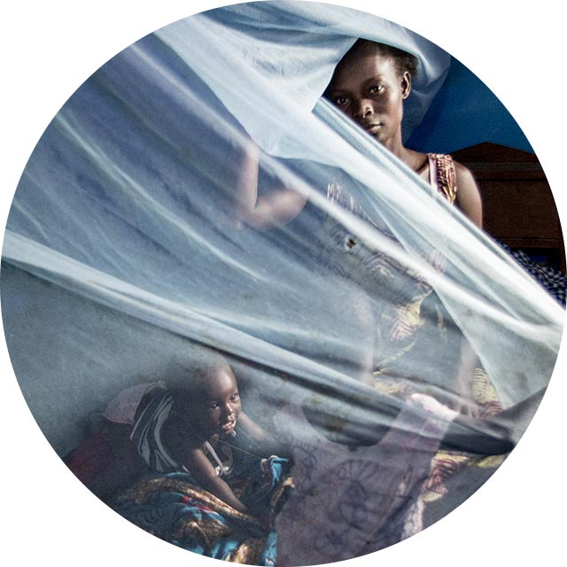 Woman putting up bed nets for her children and baby to prevent malaria infection from mosquito bites