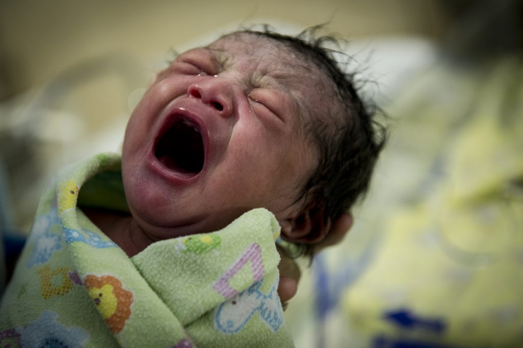 Newborn wrapped in blanket, crying.