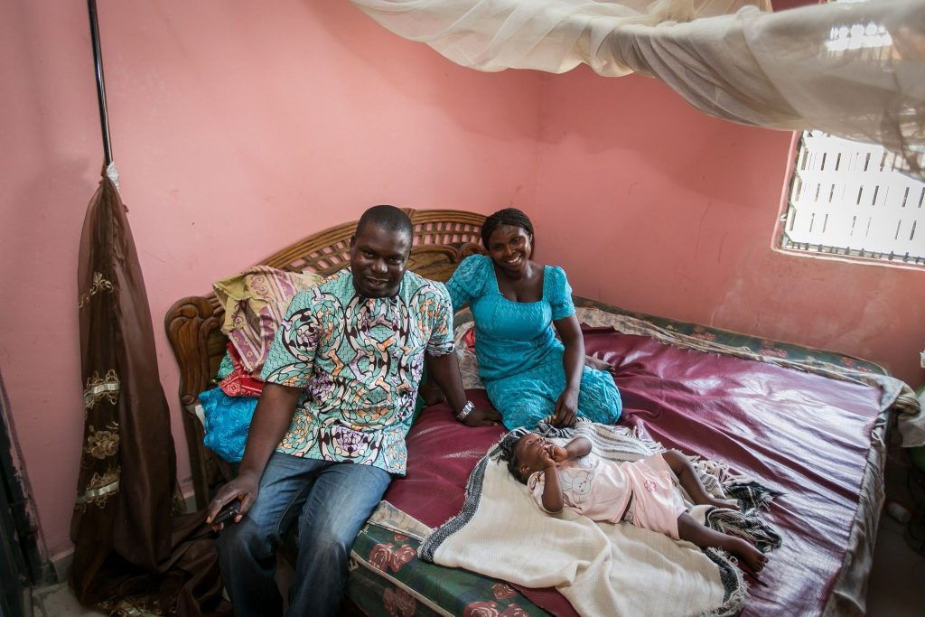 man, woman and child sitting on bed