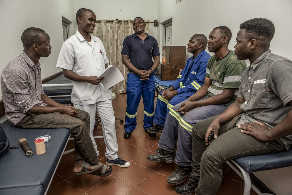 Male nurse speaking with a group of men at a health clinic.
