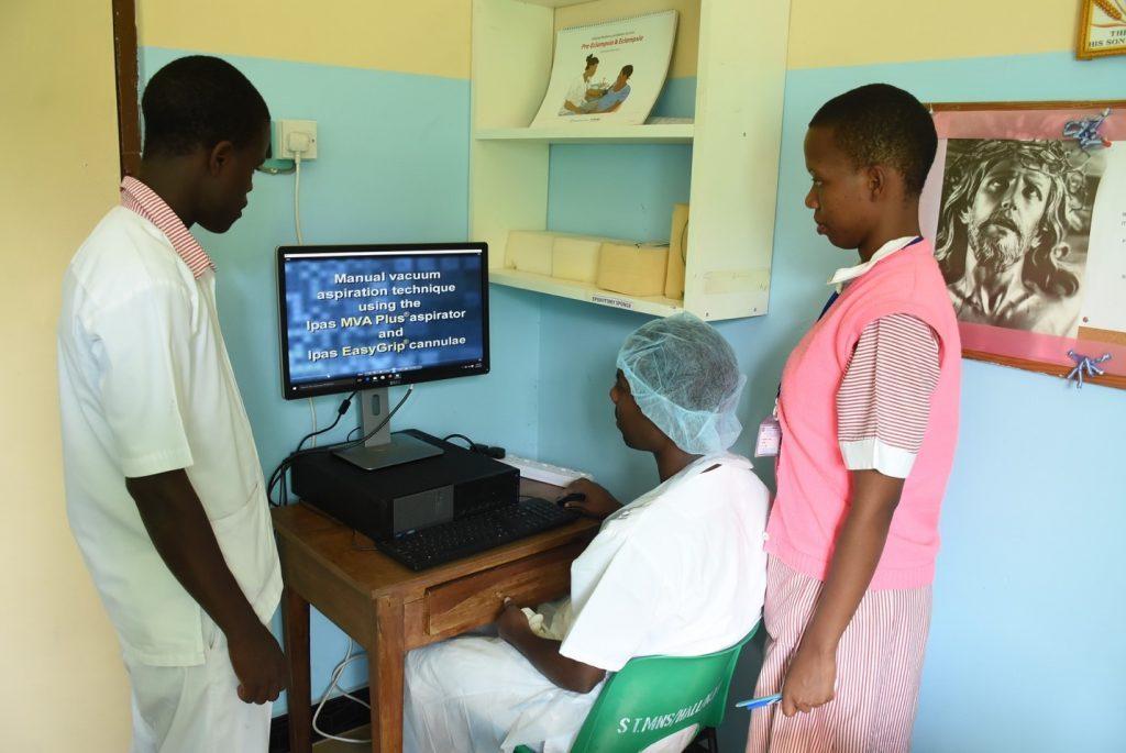 Three people looking at computer screen