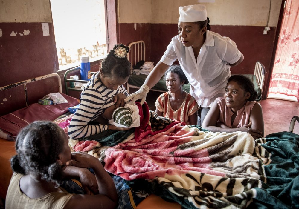 Three women gather around a new mother and baby as a nurse gives her advice about breastfeeding in a health facility.