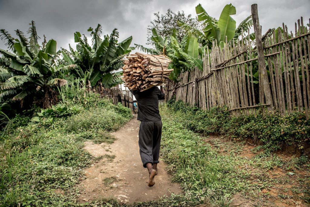 Man carries a bundle of sticks down a village road.