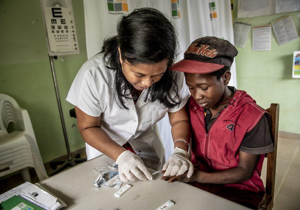 Nurse testing a young boy for malaria.