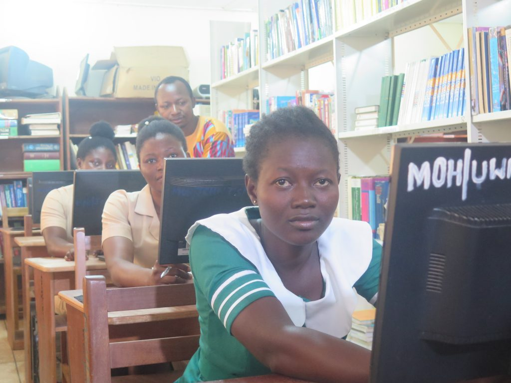 Women sitting at desks with computer screens. Photo by Emmanuel Attramah.