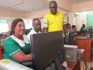 Man standing and looking at computer screen, with a man and a woman seated. Photo by Emmanuel Attramah.