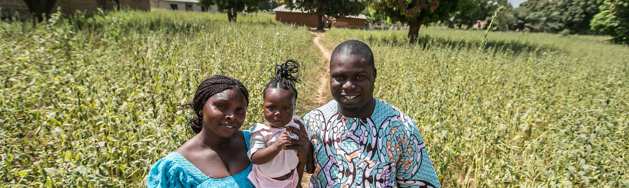 Peter Anmusku and wife Ruth  with daughter, Naomi, standing in field.