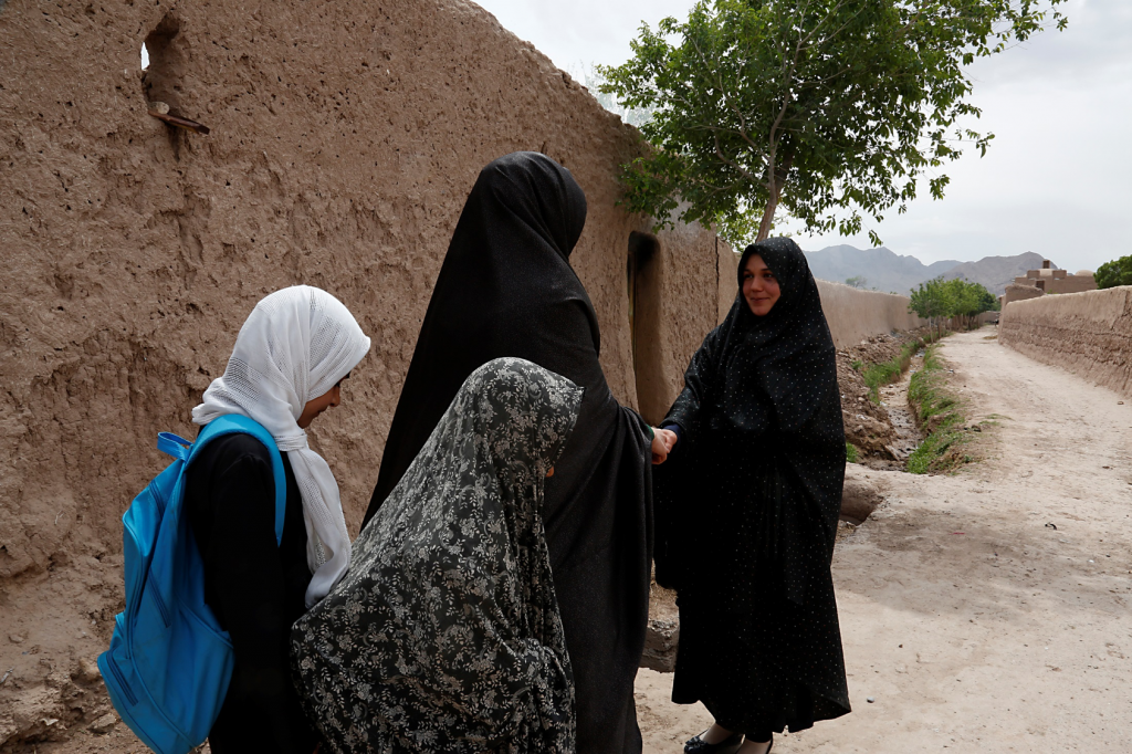 Two women greeting each other on the road outside a house. Two young girls stand behind one of the women.