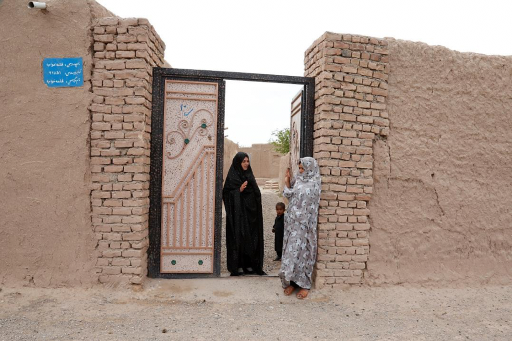Two women talking at an open gate. A small boy stands just inside.