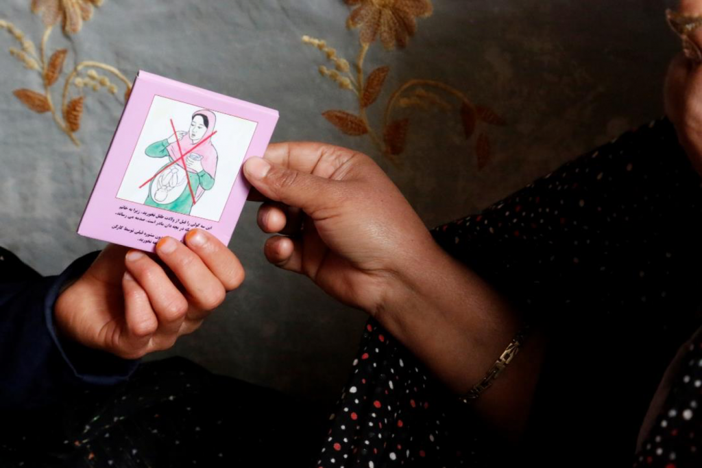 Two hands holding a misoprostol information card.