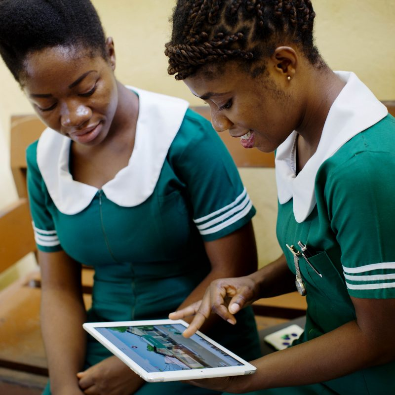 Two midwifery students viewing an app on a tablet.