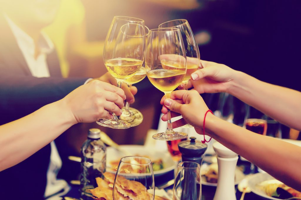 Photo of clinking glasses with white wine and toasting.