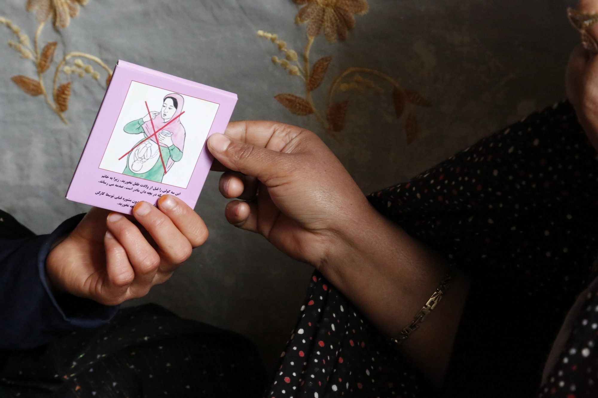 Two hands holding a small card about misoprostol.