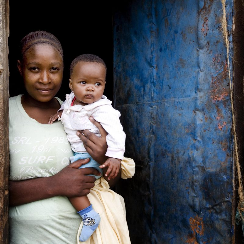 Young mother holding a baby standing in a doorway.