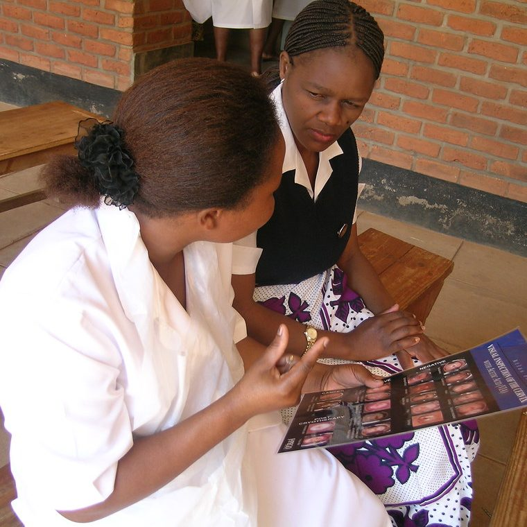 Nurse holding a chart with images and explaining to a woman sitting with her.