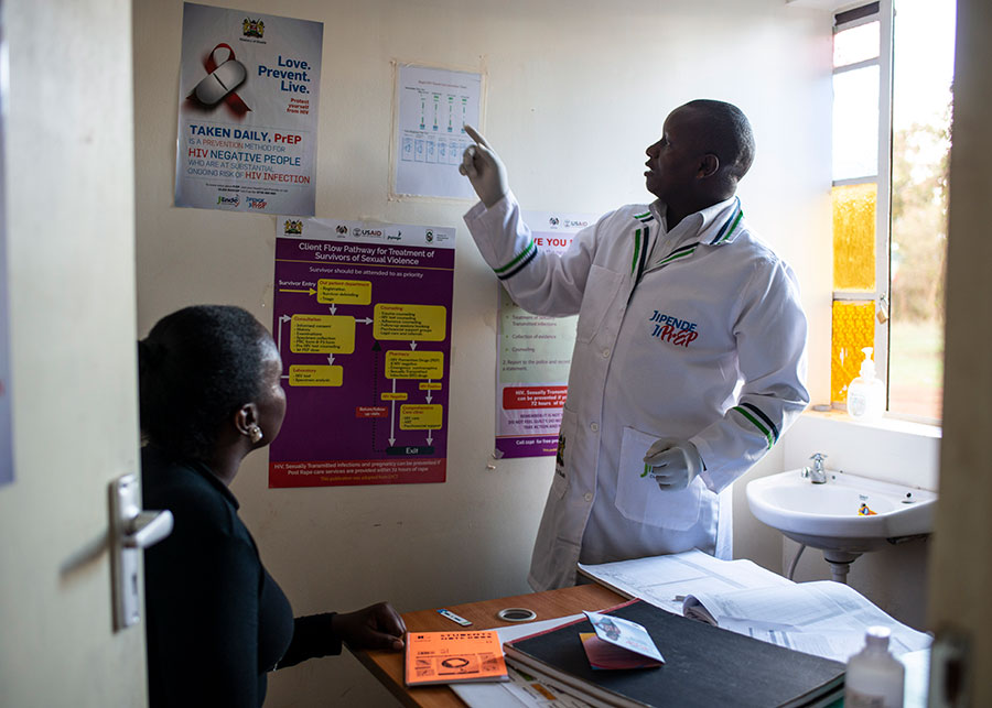 Clinician gesturing toward a wall chart while a patient observes